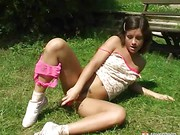 Teenage girl fucks herself in the grass
